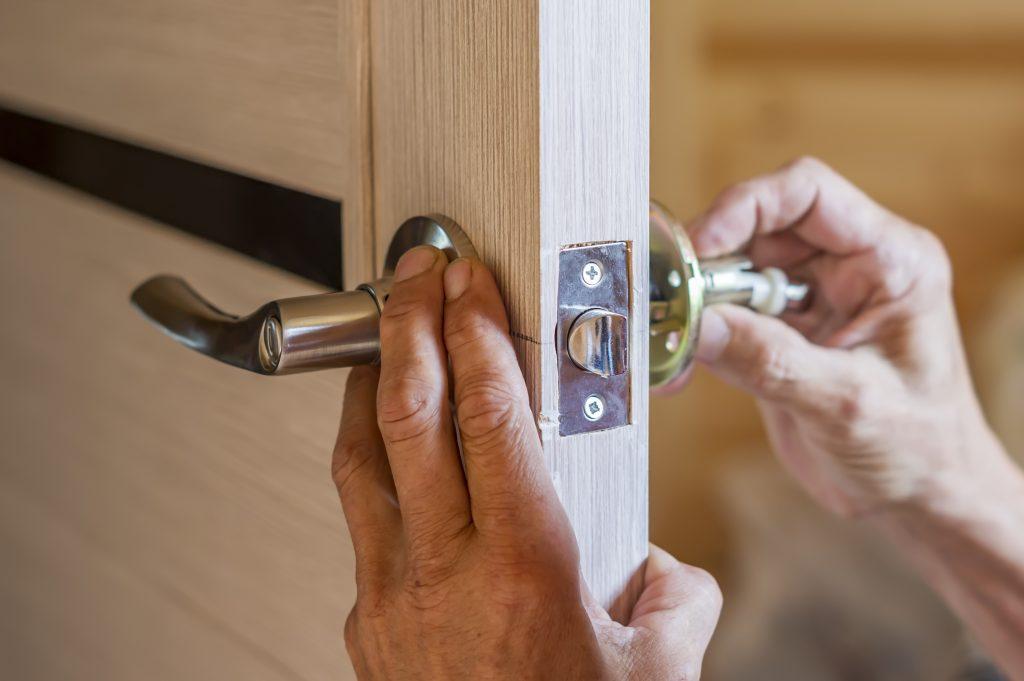 Man changing lock on door